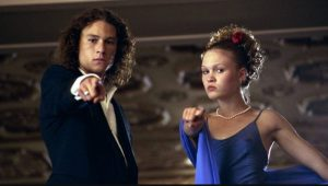 A photo of actors Heath Ledger and Julia Styles, the lead actors from the 1999 movie 10 Things I Hate About You. They are both wearing formal wear and pointing at the camera.