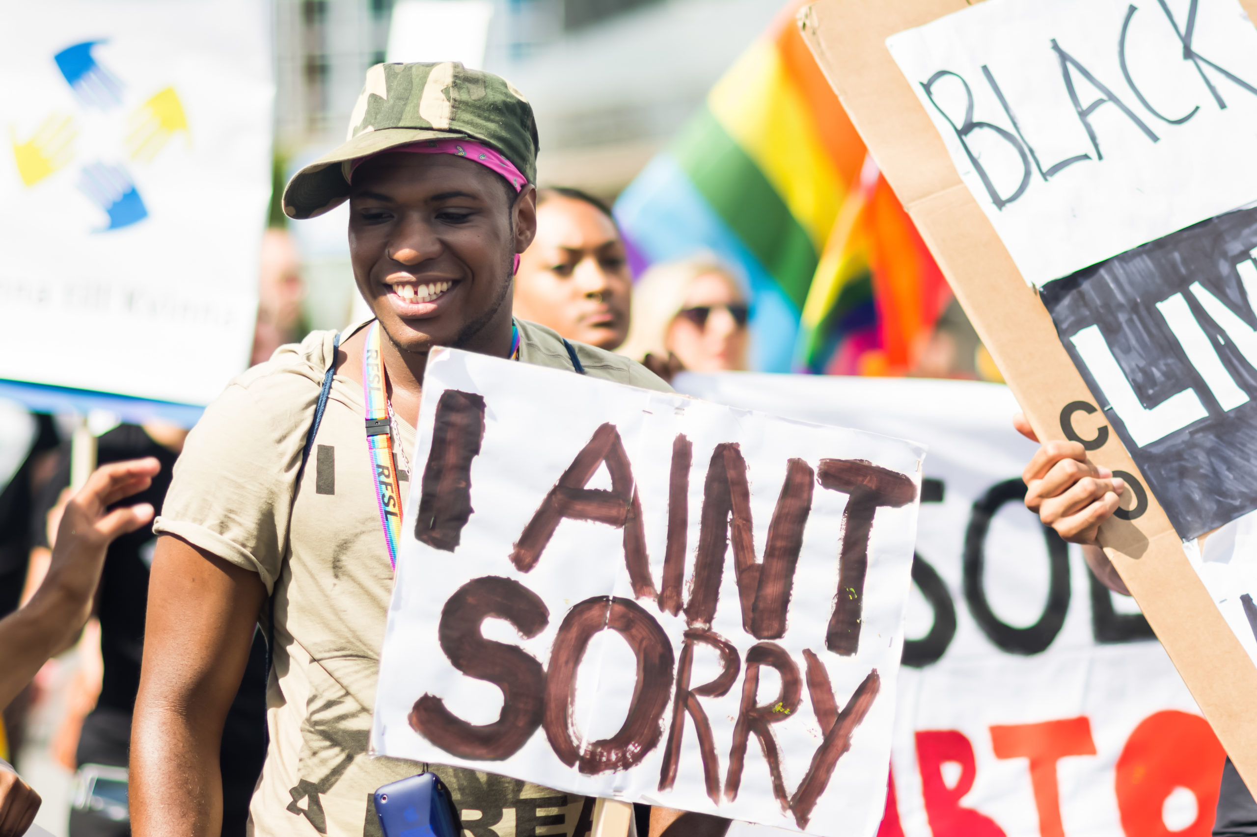 """STOCKHOLM, SWEDEN – JULY 30, 2016: Smiling Black man holding a banner that says """"I Ain't Sorry"""" during Stockholm Pride Parade on Hantverkargatan near the City Hall. A """"Black Lives Matter"""" sign and a rainbow pride flag are also visible in the crowd."""