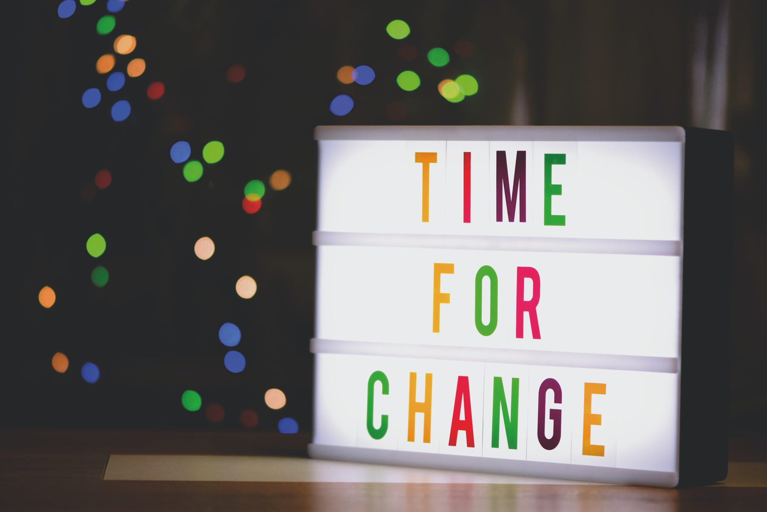 LED light box with letters in rainbow colors that spell Time for Change. Light box sits on a table and rainbow bokeh lights are in the background.