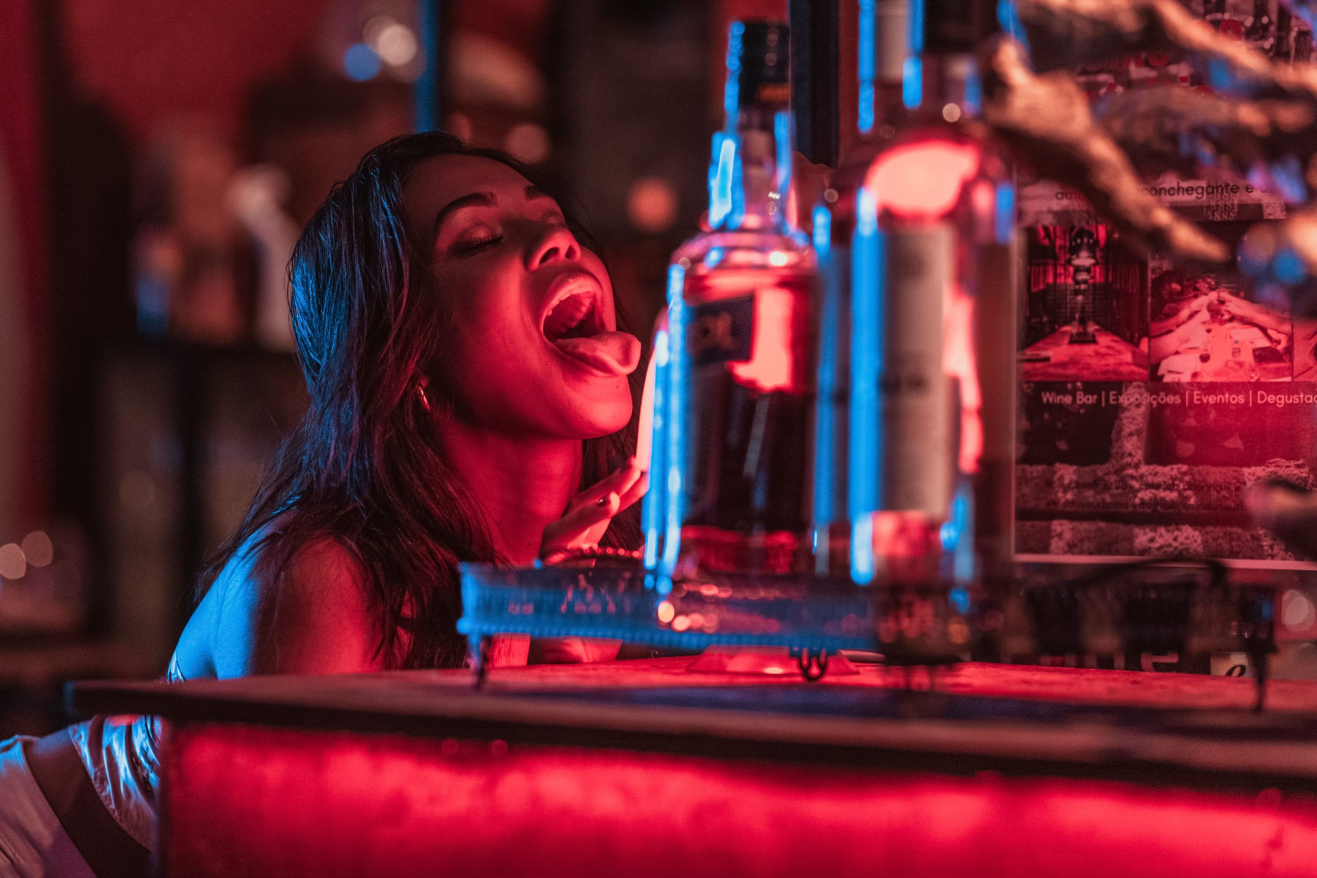 Woman at a bar leans forward to suggestively stick her tongue out at bottles of alcohol.
