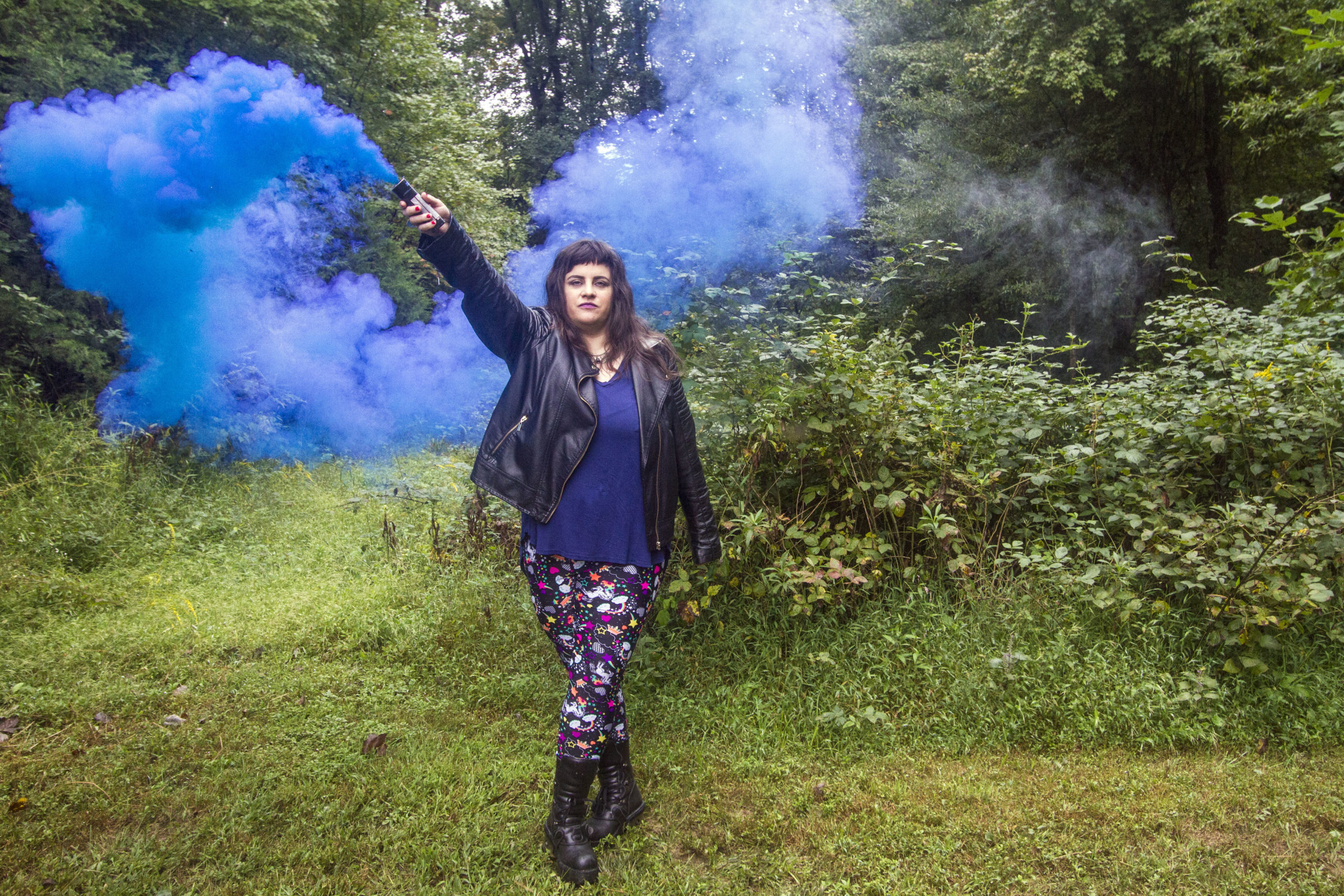 A green meadow background. I, a white nonbinary person with long brown hair, hold a blue smoke bomb up in the air. The smoke cascades behind me. I am wearing a black leather jacket, a navy blue shirt, large black boots, and black leggings with a print of unicorns and rainbows.